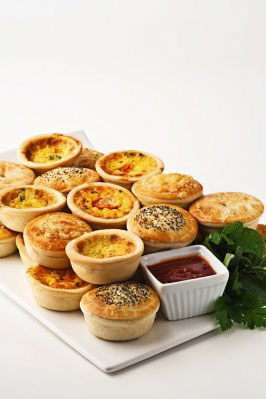Mini quiches and pies placed in two layers on white platter, alongside some parsley and a small dish of tomato sauce
