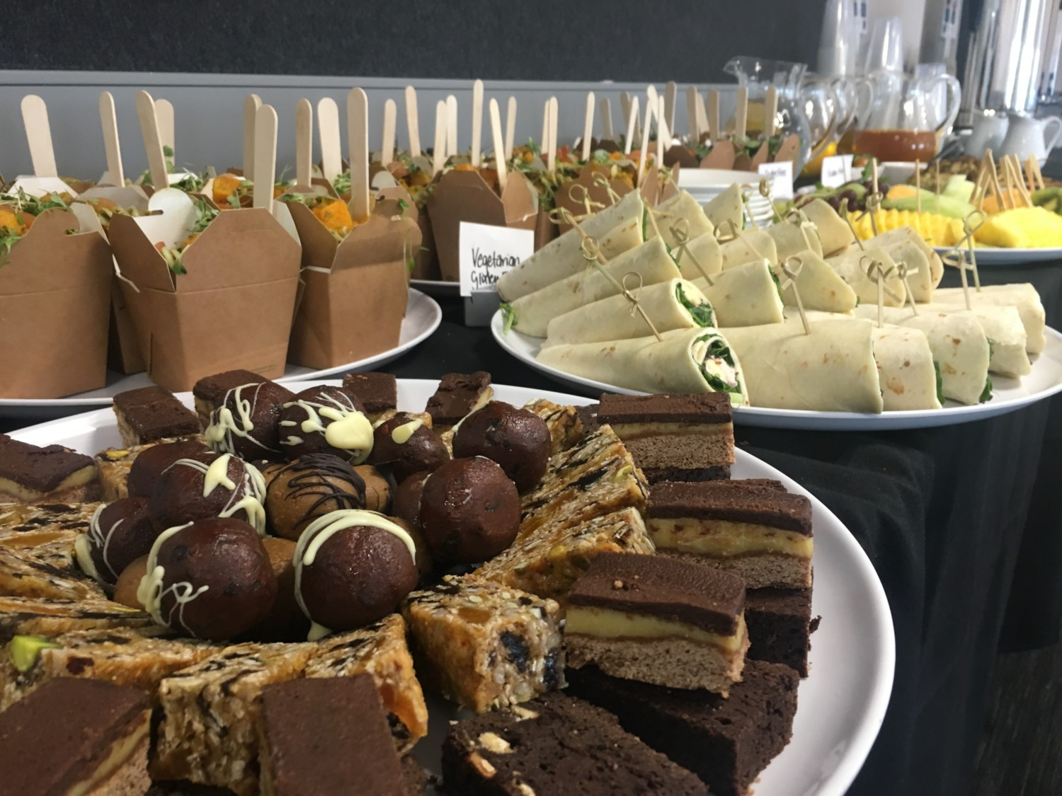 boxed salads, wraps, cakes and slices at a buffet