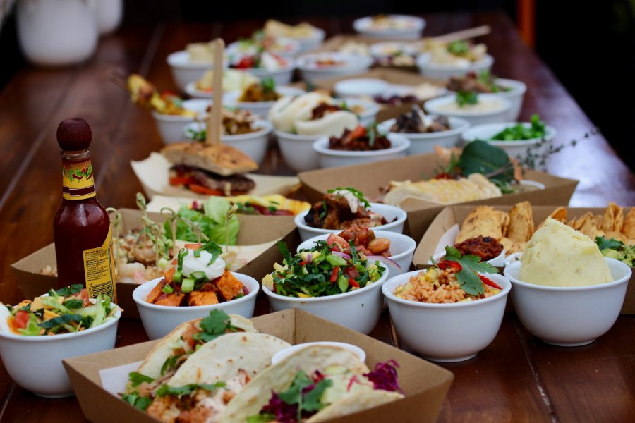 Wooden table laden with small bowls and boxes of tacos, meats and salads